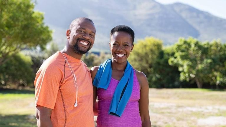 Couple on a run outdoors smiling | Dentist in Fort Collins